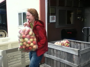 FDN volunteer, Ivy Miller, picks up a donation of apples from Cornell Orchards for distribution to local food pantries.